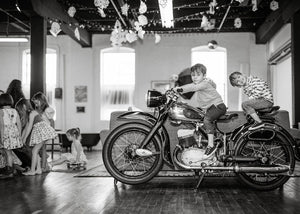 black and white picture with 2 boys on a motorcycle