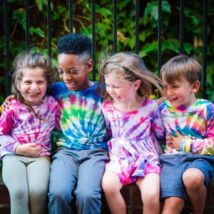 kids in tie dye laughing on a bench