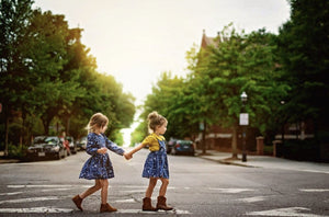 Girls pinafore dress and STEM clothing modeled by two girls holding hands walking across city street.  Unique toddler clothing with matching sibling outfits available!