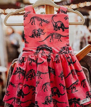 close up shot of baby dinosaur dress in pink.  Our favorite baby and toddler pinafore dress!