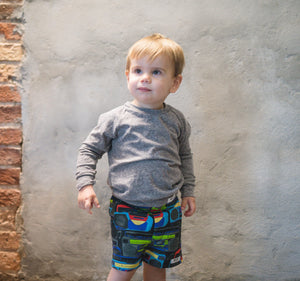 Toddler modeling baby printed shorts in Boombox print and grey infant raglan tee. Unique baby clothing
