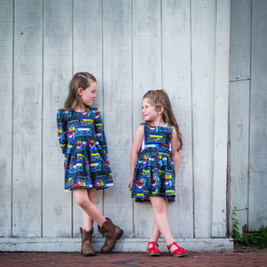 Two girls looking at each other wearing boombox print dresses.  Toddler & baby pinafore dress, retro baby clothes featured.  Matching sister outfits newborn and toddler available!