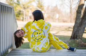 Mom and daughter in matching tie dye loungewear sets with smiley face embroidered on back