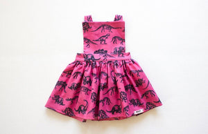 Dinosaur dress girl.  Magenta pink girls pinafore dress with dinosaur print available in matching sister outfits newborn and toddler.