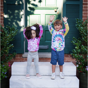 Tie dye baby clothes by Worthy Threads clothing brand!  Girl wearing pink and purple tie dye raglan and boy in tie dye hoodie with hands raised.  Unique toddler clothes