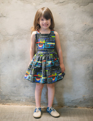 Girl modeling pinafore dress in boombox print: unique kids clothing by Worthy Threads brand