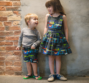 Matching sibling outfits in Boombox print: bro and sis modeling baby shorts, infant raglan tee, girls pinafore dress.