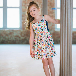 Girl modeling toddler pinafore dress in sushi print.  Unique toddler clothing by Worthy Threads brand