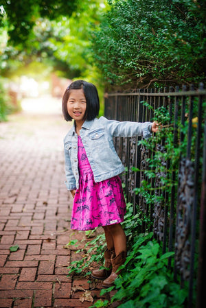 Girl by fence in pink dinosaur dress and jean jacket.  Girls pinafore dress style.