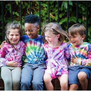 Four kids wearing kids tie dye clothing.  Unique kids clothing with matching sibling outfits available!