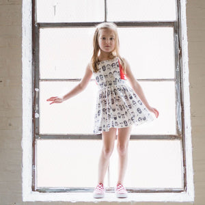 Baby pinafore dress in Beatnik print modeled by girl standing in windowsill.  Unique toddler clothes by Worthy Threads clothing brand with sibling coordinating outfits available!
