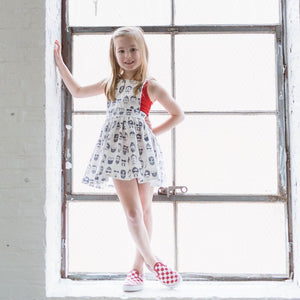 girl leaning on the wall on a windowsill in a red tank top, red van sneakers and a black and white printed dress with men with mustaches and beards.  Matching sibling outfits available!