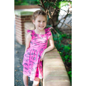 girl leaning on brick ledge in a pink dino ruffle dress.  Unique kids clothing available in matching sister outfits newborn and toddler.