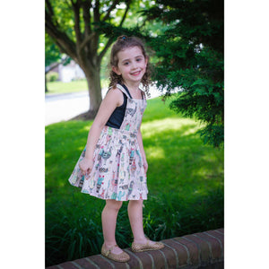 Girls pinafore dress: Girl standing on brick wall in a pink llama print dress