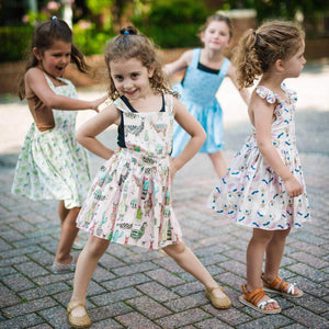 Girls pinafore dress: girl posing in a group of friends wearing pink llama print dress