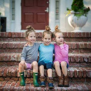 Three girls sitting on brick stairs each in a different color youth and infant raglan tee shirt.