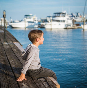 Boy sitting on dock wearing grey hoodie with Beatnik hood lining by Worthy Threads, brand for unique kids clothing