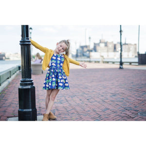 Girl swinging from light post wearing toddler pinafore dress, hedgehog dress.  Hedgehog baby clothes by Worthy Threads clothing brand available in sibling coordinating outfits