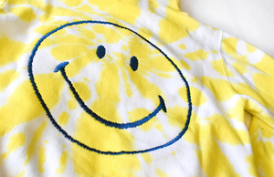 Adult tie dye hoodie in yellow with embroidered smiley face on back