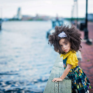 Toddler wearing girls pinafore dress in Canning fabric over mustard collared shirt leaning over Baltimore Harbor barrier.  Unique toddler clothes for you tiny style icon.