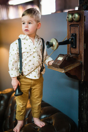 Toddler boy Button Down Shirt with bees featured.  Boy holding a phone receiver while standing on the arm of a couch.