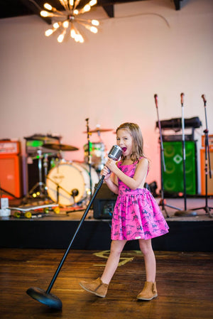 Girl singing into microphone in a pink Toddler pinafore dress with dinosaurs printed all over.