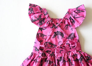 Close up of back of girls ruffle sleeve dress in dino.  Girls dinosaur clothes available in matching sister outfits newborn and toddler!