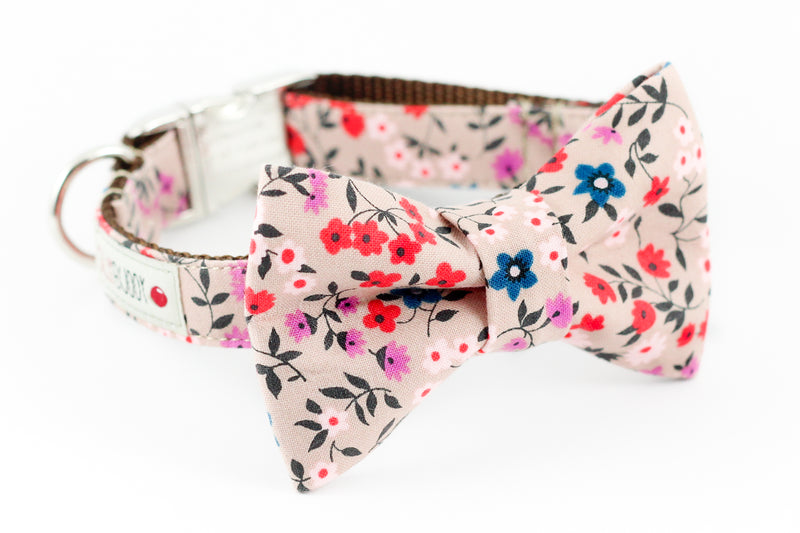 Light pink dog bowtie collar with red and blue floral print.