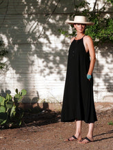 Model standing in courtyard with hands in pockets wearing The Barb dress