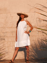 Model against wall wearing white linen Summer Dress