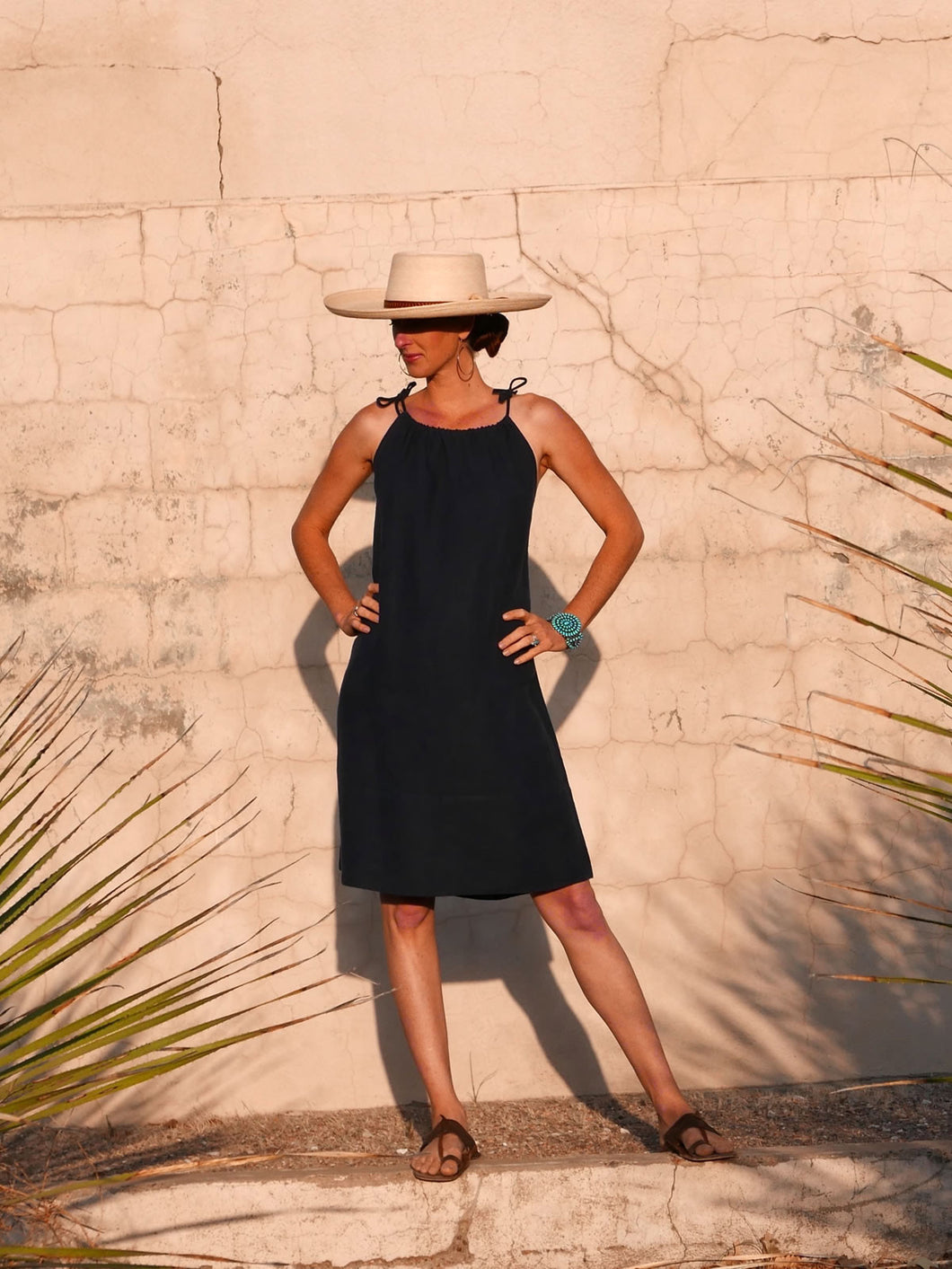 Model against wall wearing black linen Summer Dress