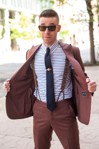 guy wearing suspenders with a suit on the street