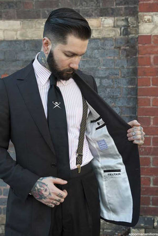 man wearing suit and suspenders to a wedding