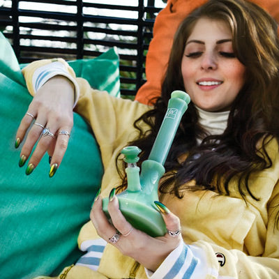 young brunette woman with long green nails smoking a pipe