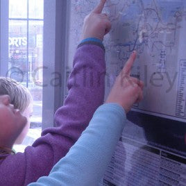 children pointing on map