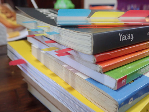 A stack of books with post-it note flags sticking out of the pages.