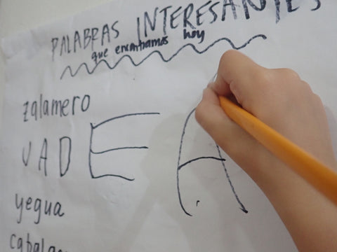 """A child adds to a classroom chart called """"Palabras Interesantes"""""""