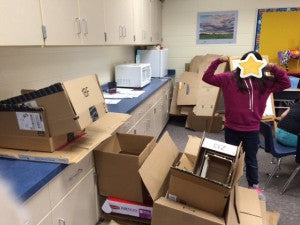 Photo of a student in a classroom, standing amidst a large collection of cardboard boxes.