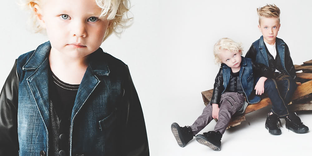 Two little boys in stylish street wear with leather and denim jackets and high fashion denim pants.