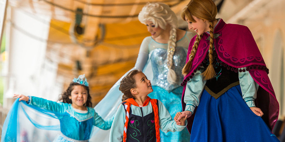 Disney princesses Anna and Elsa befriending a little boy and a little girl in Disney apparel.