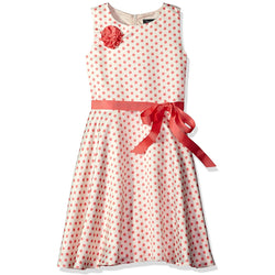 White sleeveless knee-length dress with pink polka dots, coral grosgrain flower accent on lapel, and matching waist bow sash