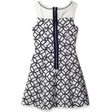 Back of White and navy blue cloverleaf patterned knee-length sleeveless dress with solid white yoke and navy contrast piping