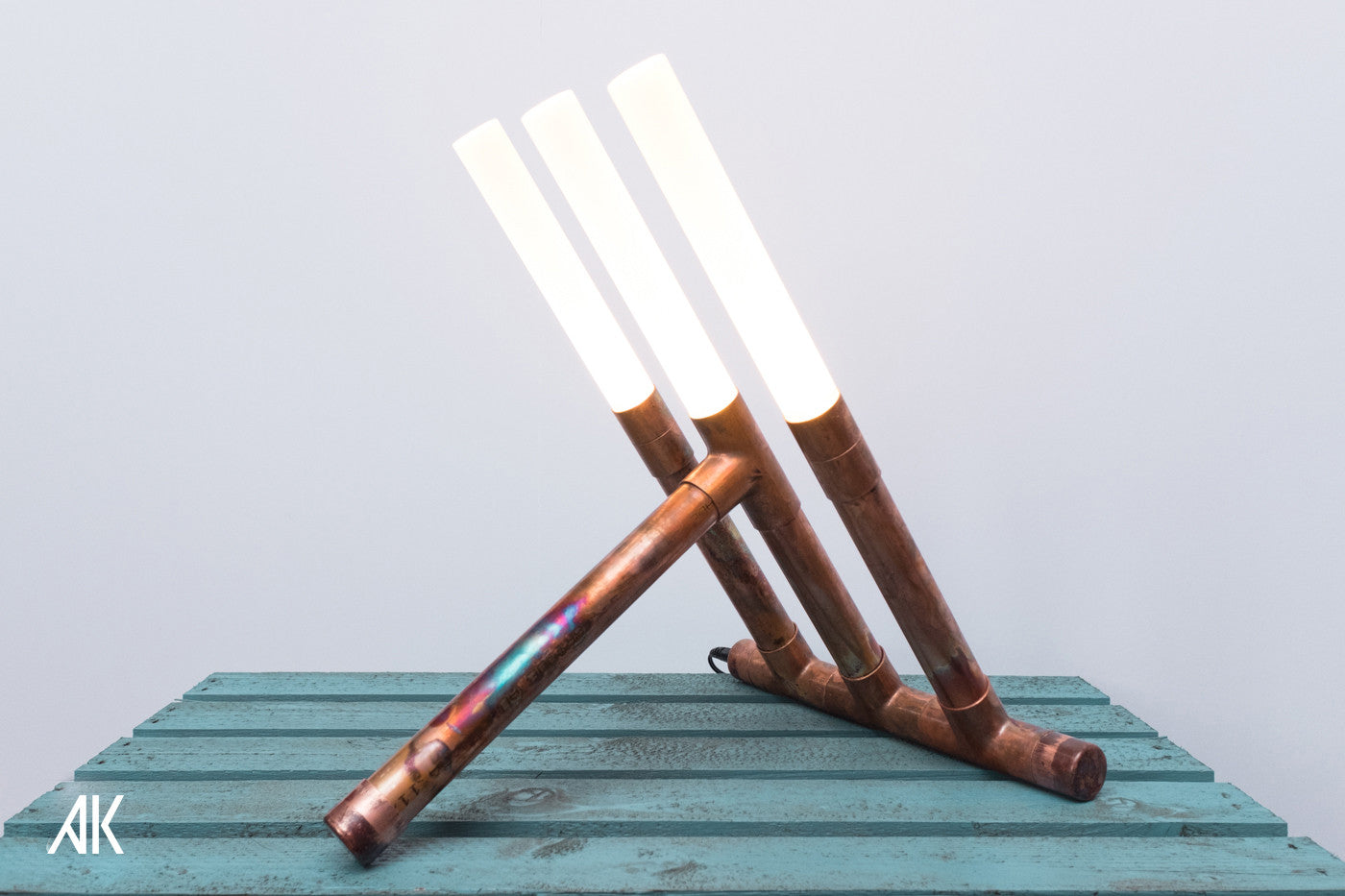 A copper pipe lamp with three cylindrical LED light shafts.