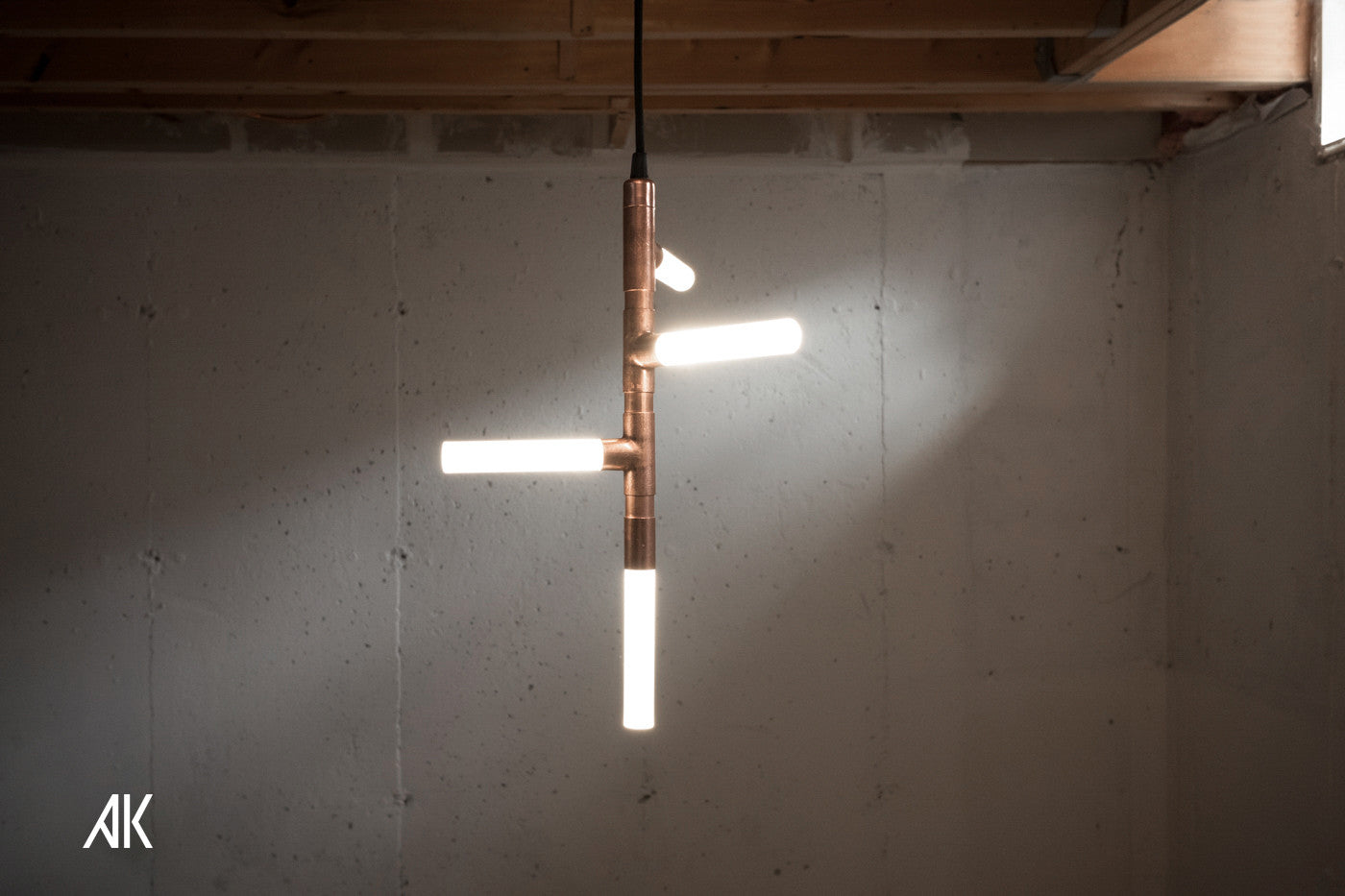 An abstract pendant light made with copper pipe, resembling tree branches.