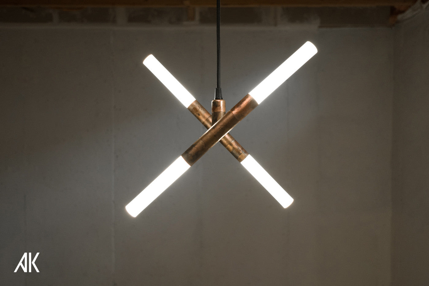A geometric pendant lamp made with copper pipe, resembling a cross.