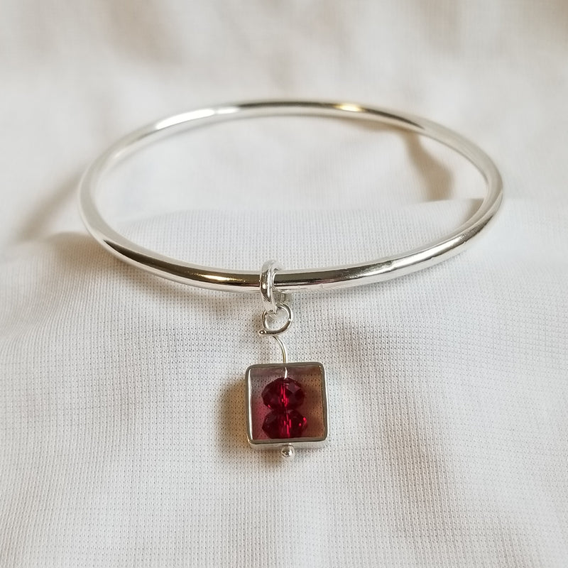 Bangle with red crystals and square charm