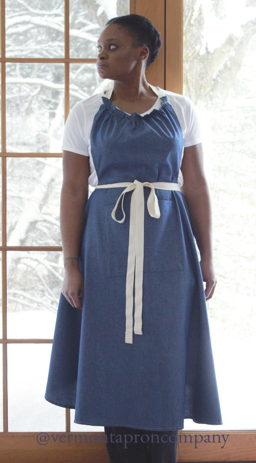 The Long Kitchen Apron in denim by The Vermont Apron Company hangs to mid calf, wraps around your body for complete coverage and ties in front.