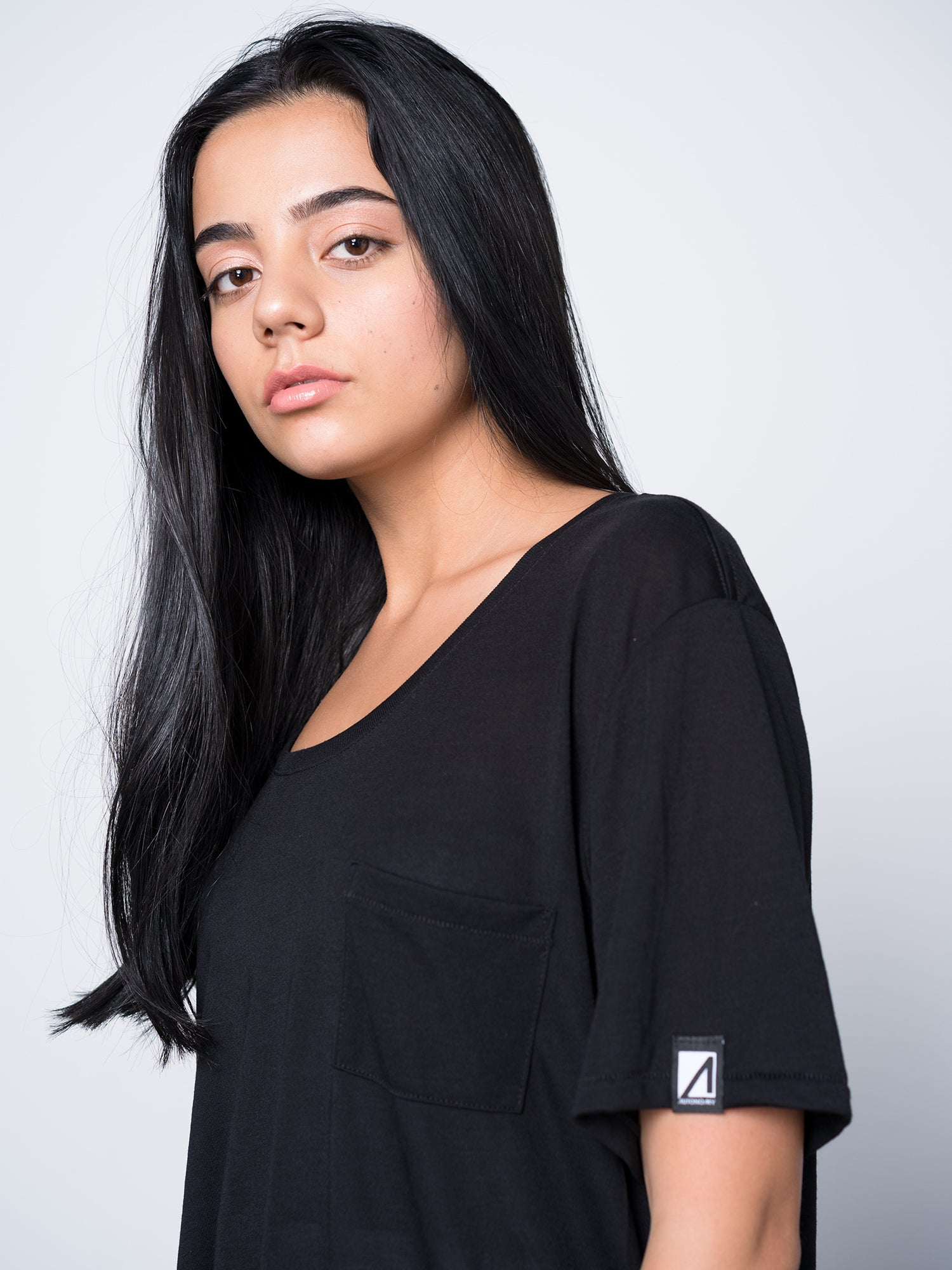Side view of girl skateboarder wearing black Autonomy Arco shirt