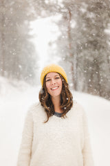 Old Pine Candle Co communications manager stands on a snowy mountain road, looking at the camera, wearing a yellow knit hat and an oversized white sweater as the snow falls around her.