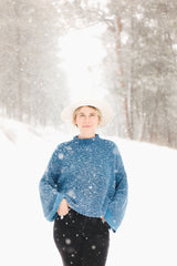 Old Pine Candle Co owner Danielle Rooney stands on a snowy mountain road with the snow falling around her wearing a white Stetson hat, oversized blue sweater, and black jeans with her hands in her pockets and her legs crossed.